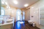 Baño con suelo de madera y paredes en mármol