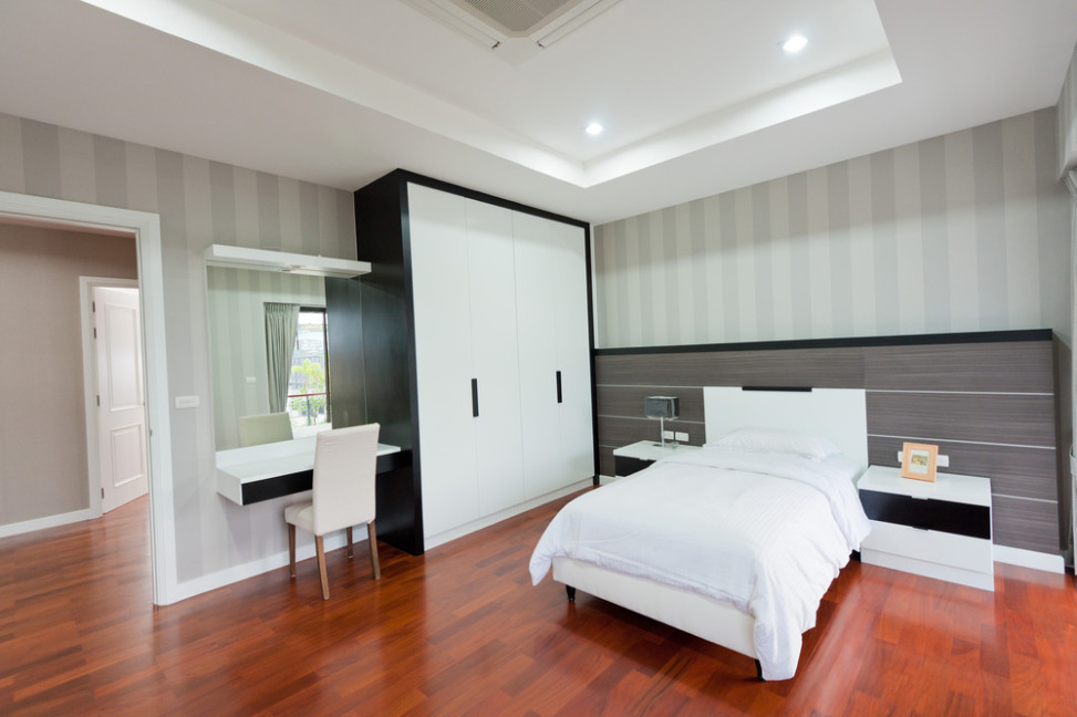 Dormitorio con suelo de parquet y muebles blancos y negros for Dormitorio blanco y madera