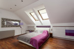 Dormitorio en buhardilla con suelo de parquet