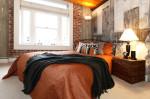 Dormitorio industrial con pared de ladrillo visto