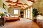 Dormitorio rústico con vigas vistas de madera