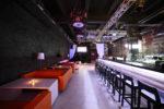 Pub estilo industrial con sofás naranjas